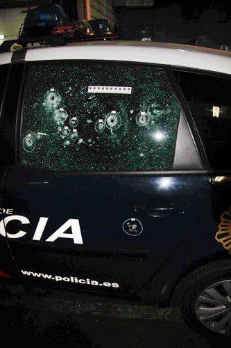 Impactos de bala en el cristal de un vehículo de la policía Nacional