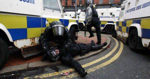 Policía herido asistido por otro policía en los disturbios de Belfast en el año 2013